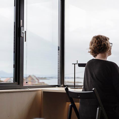 woman at desk in front of large windows looking out over coastline view
