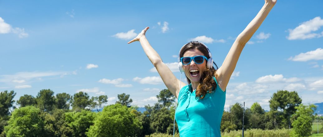 cheerful young woman wearing sunglasses and raised hands on the sunroof of a car