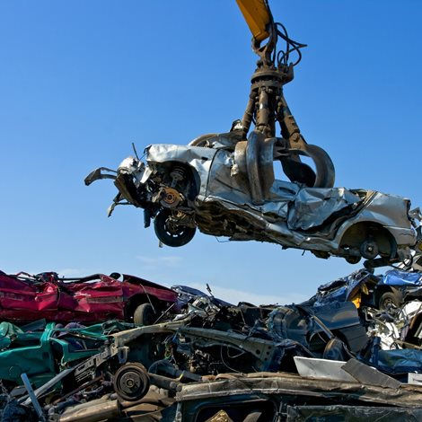 Large crane holding wrecked car over heap of scrap metal