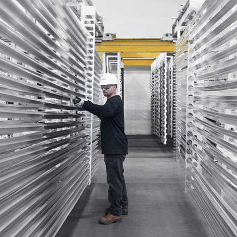 Worker inspecting long extruded rods of aluminium on shelves