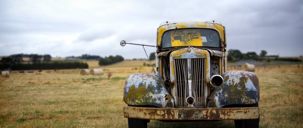old rusted car in a field